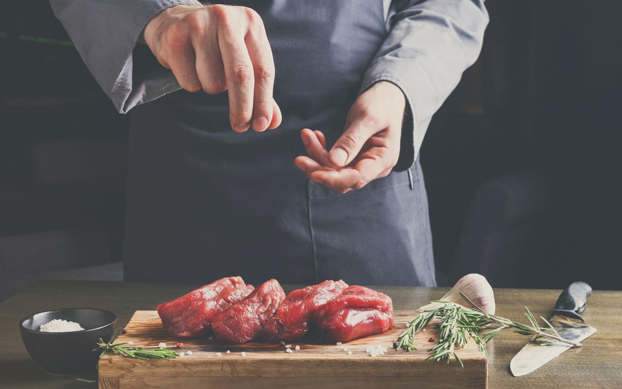 Mann bestreut ein Filet Mignon Steak mit Pfeffer und Salz